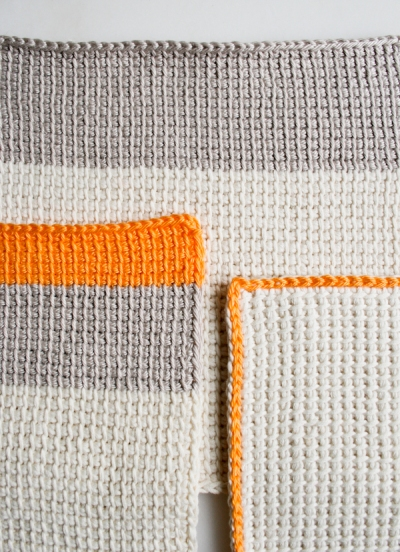 Tunisian crochet washcloths in orange and grey yarn by the Purl Bee